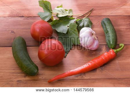 Products for home canning on the plate. Cucumbers tomatoes peppers garlic the leaves of red currant