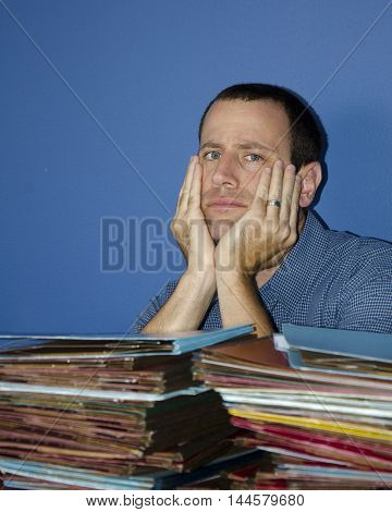 Stressed at work. Young man at desk with hands on his cheeks stressed out by all the files in front of him.