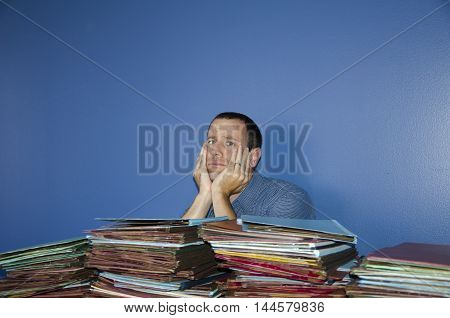 Young man at desk with hands on his cheeks stressed out by all the files in front of him.