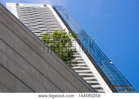 Low angle view of two cleaners haning high on ropes and cleaning glass windows of a modern building under blue sky.