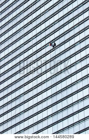 A cleaner with good safety equipment hanging high and cleaning many glass windows of a modern building.