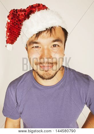 funy exotical asian Santa claus in new years red hat smiling on white background
