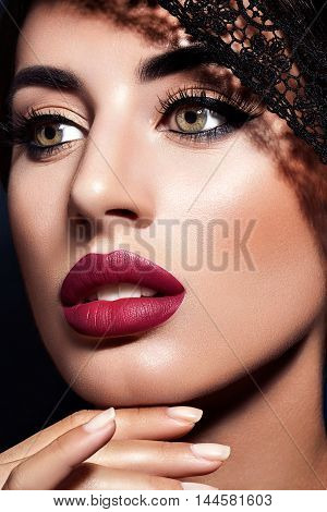 Portrait of a beautiful glamorous brunette with bright make up. Red lips. Close-up, beauty