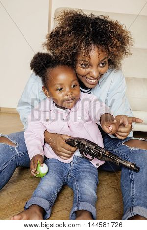 adorable sweet young afro-american mother with cute little daughter, hanging at home, having fun playing smiling, lifestyle people concept