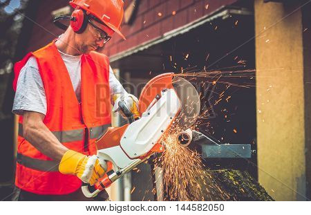 Construction Worker with Metal Cutter While Cutting Metal Pipe. Caucasian Worker.