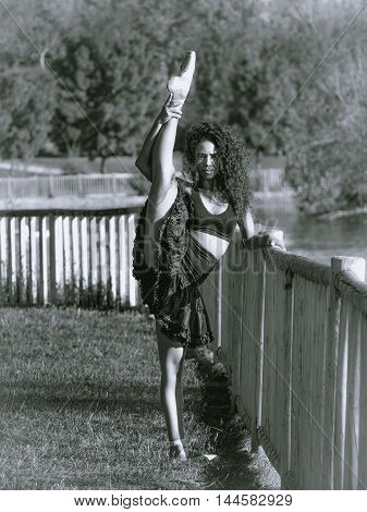 Latino dancer in a park with raised leg monochrome