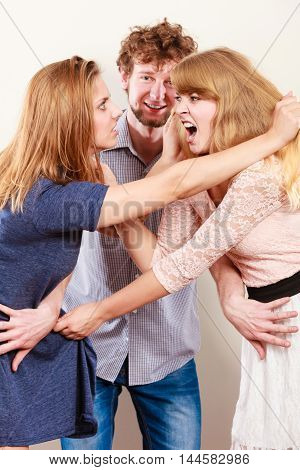 Aggressive mad women fighting over man. Jealous girls wooing guy. Violence.