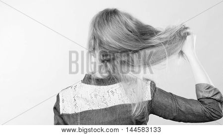Hairstyle and hairdo. Haircare concept. Back view of blonde woman playing with straight long hair. Hairstylist barber making coiffure.
