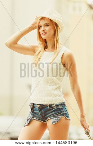 Summer time and vacation. Attractive young woman spending holidays on travelling. Joyful smiling blonde girl relaxing in city.