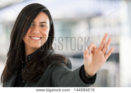 Smiling woman making OK sign. Focus on the hand