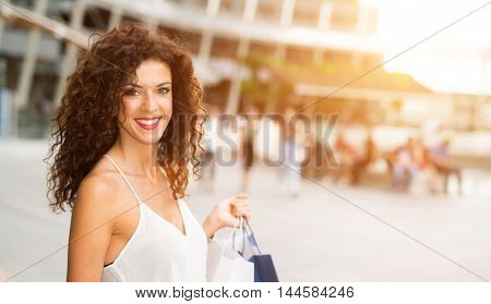 Woman shopping in a city. Bright light effect in the background