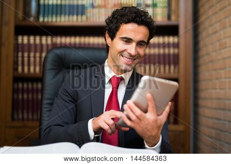 Smiling business man using a tablet