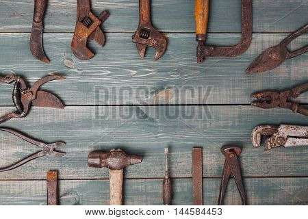 different rusty construction instruments on the green wooden background.