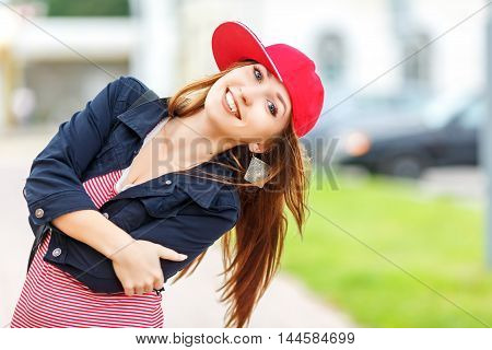 Fashion city portrait of stylish hipster woman with milk shake, sunglasses, red striped dress, red cap and sneakers, makeup, long brunette hairs, walking alone at weekend, enjoy vacation in Europe, modern trendy summer outfit. Evening soft sunlight.