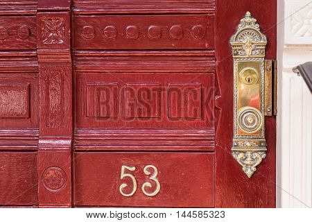 A detailed old red main door with the number fifty three