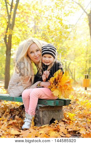 Mother and daughter have a fun in autumn park, lying in yellow autumn foliage and looking each other, top view happy lifestyle concept, outdoor