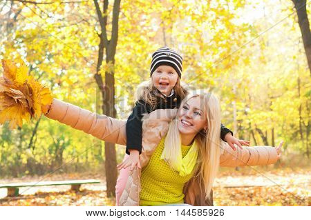 Mother and daughter have a fun in autumn park, happy motherhood concept, outdoor