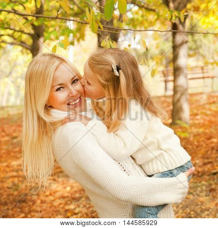 Little girl kissing her mother, smiling mother holding little baby girl, autumn outdoor