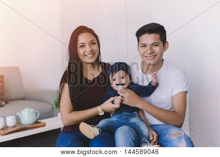 Young latin couple with a six month baby sharing a happy moment in their home