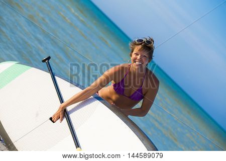 Healthy woman practicing paddle board in the Caribbean