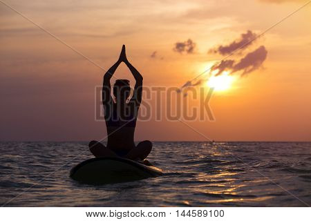 Woman practicing SUP yoga at sunset, meditating on a paddle board.