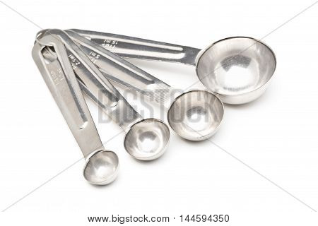 Set of empty metal measuring spoons over white background