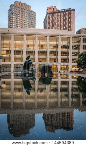 New York United States - June 20 2016: view of Henry Moore's bronze sculpture Reclining Figure (1965) in the pond basin at Lincoln Center with the reflaction. At same time the reflaction also includes the Every Fisher Hall in the background and highrise o