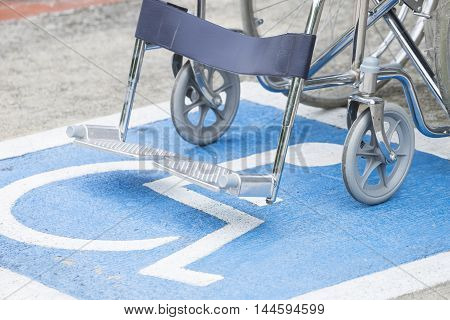 Pavement handicap symbol and wheelchair in the car park