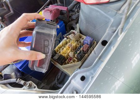 The man opening fuse box of old car