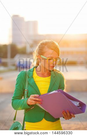 Business woman holding a folder. Girl in glasses and jacket carefully checks documents.