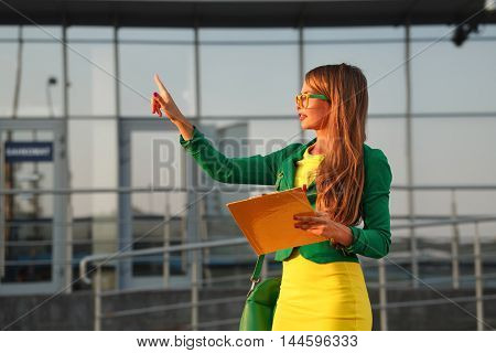 Business woman controls the works. Young attractive girl in glasses and jacket holding a checklist.