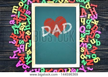 Love Dad text on school board and magnetic letters