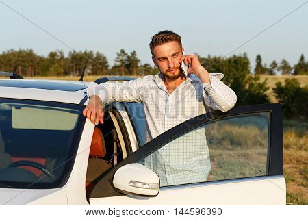 Young handsome man opened the door of his car. Man talking on the phone. Always connected.