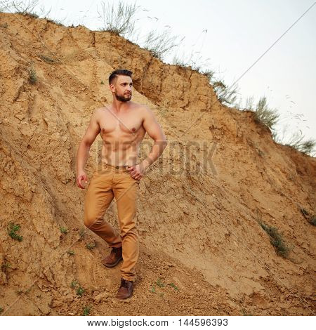 Young handsome man descends into a sand pit. Muscular man with a fashionable hair and beard.