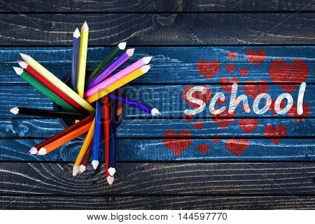Love School text painted and group of pencils on wooden table
