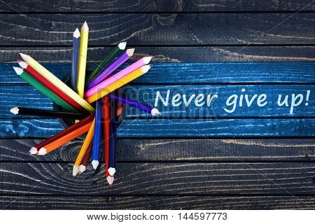 Never give up  text painted and group of pencils on wooden table