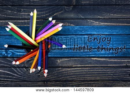 Enjoy little things text painted and group of pencils on wooden table