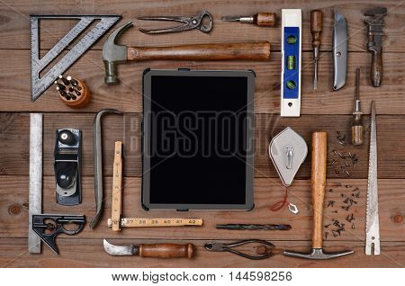 High angle shot of an assortment of contractors well used tools. Horizontal format on a rustic wood background, with a tablet computer in the middle of the tool arrangement.