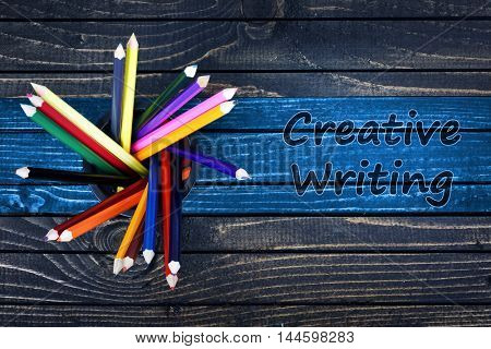 Creative Writing text painted and group of pencils on wooden table
