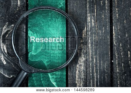 Research text painted and magnifying glass on wooden table