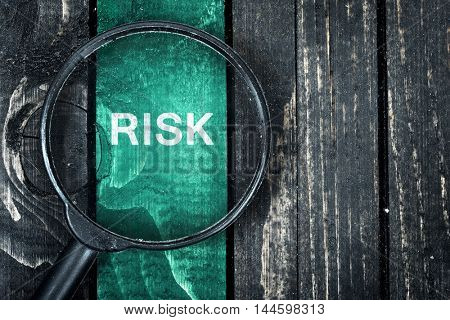Risk text painted and magnifying glass on wooden table