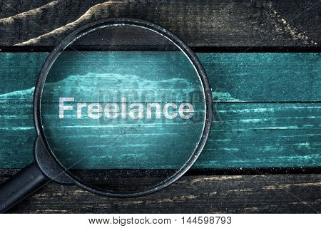 Freelance text painted and magnifying glass on wooden table