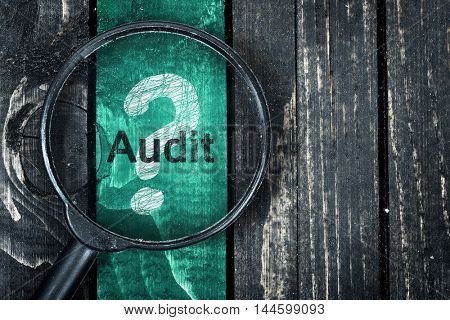 Audit text painted and magnifying glass on wooden table