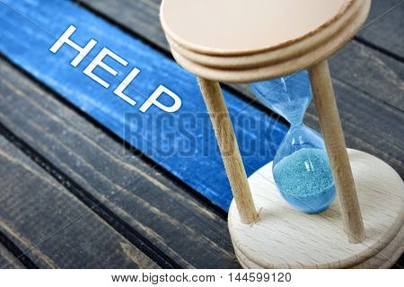 Help text and hourglass on table on wooden table
