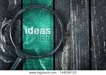 Ideas text painted and magnifying glass on wooden table