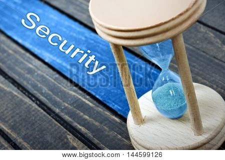 Security text and hourglass on wooden table