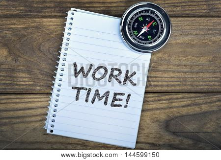 Work time text and metallic compass on wooden table