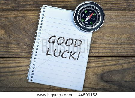 Good Luck text and metallic compass on wooden table