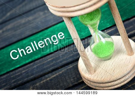 Challenge text and hourglass on wooden table