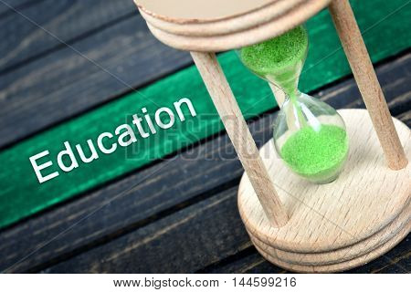 Education text and hourglass on wooden table